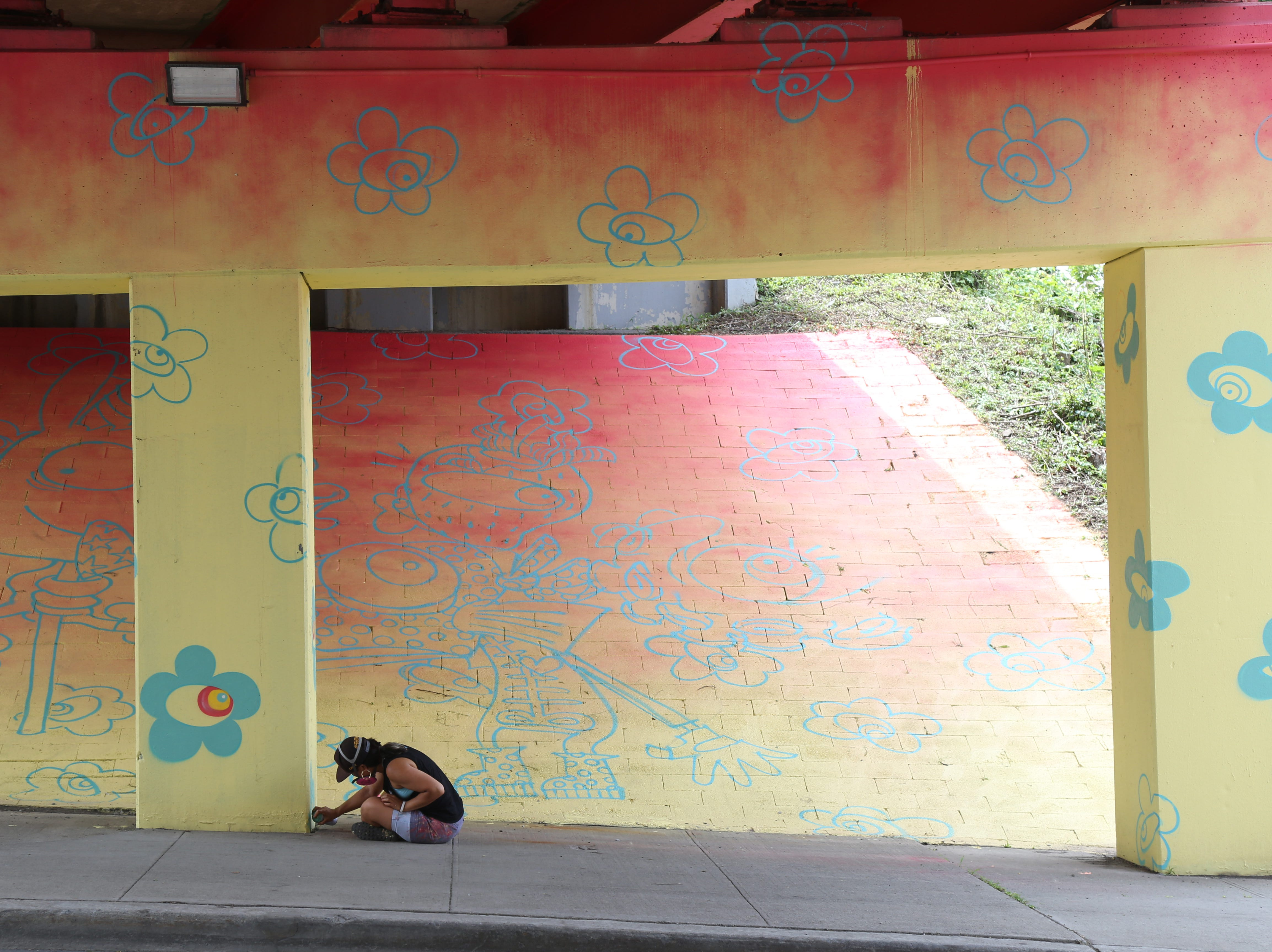"""Risa Tochigi, """"Boogie"""" of BoogieREZ, works on the Poughkeepsie Gateway mural, on the Route 9 Underpass at Main Street in the City of Poughkeepsie, on July 27, 2018. The mural was commissioned by the Poughkeepsie Alliance in collaboration with Arts Mid-Hudson and the O+ festival."""