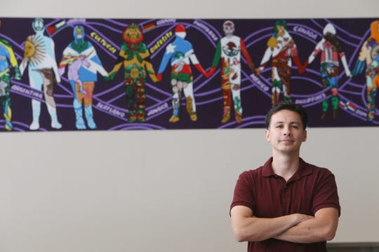 Joe Pimentel, a freelance art teacher with one of the murals he worked with students to create inside the Titusville Intermediate School in the Town of Poughkeepsie on July 13, 2018.