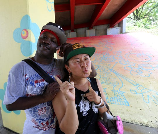 "From left, TC Weaver, ""REZ,"" and Risa Tochigi, ""Boogie"" of BoogieREZ, pose with their mural on the Route 9 Underpass at Main Street in the City of Poughkeepsie on July 27."