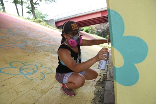 "Risa Tochigi, ""Boogie"" of BoogieREZ, works on the Poughkeepsie Gateway mural, on the Route 9 Underpass at Main Street in the City of Poughkeepsie, on July 27, 2018. The mural was commissioned by the Poughkeepsie Alliance in collaboration with Arts Mid-Hudson and the O+ festival."