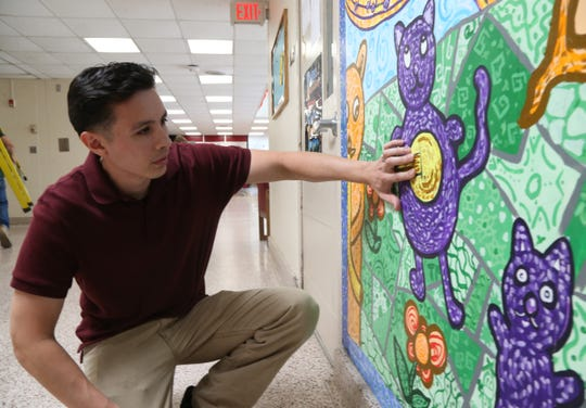 Joe Pimentel, a freelance art teacher with points out details on one of the murals he worked with students to create inside the Titusville Intermediate School in the Town of Poughkeepsie on July 13, 2018.