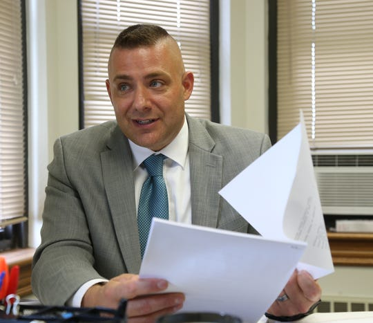 Dutchess County Assistant District Attorney Anthony Parisi holds a copy of an indictment for multiple alleged gang members in his City of Poughkeepsie office on Thursday.