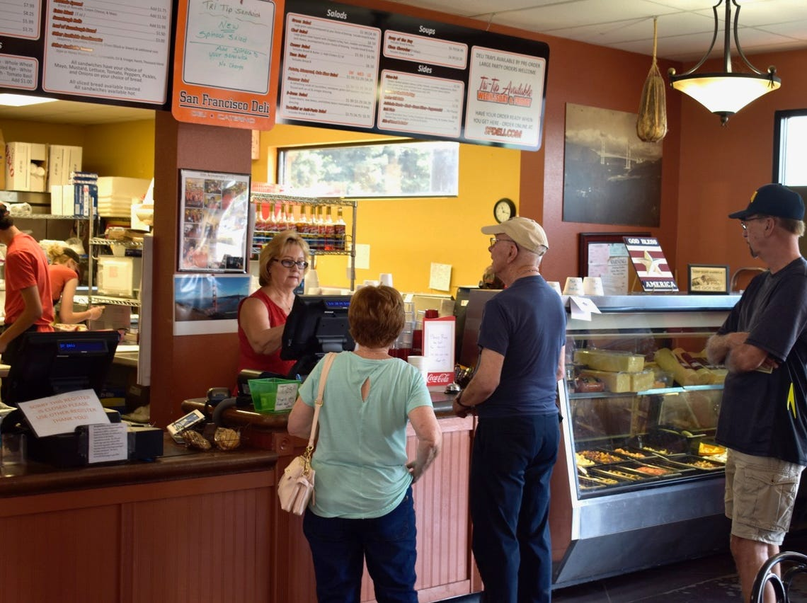 Customers line up to place lunch orders at San Francisco Deli in Redding.