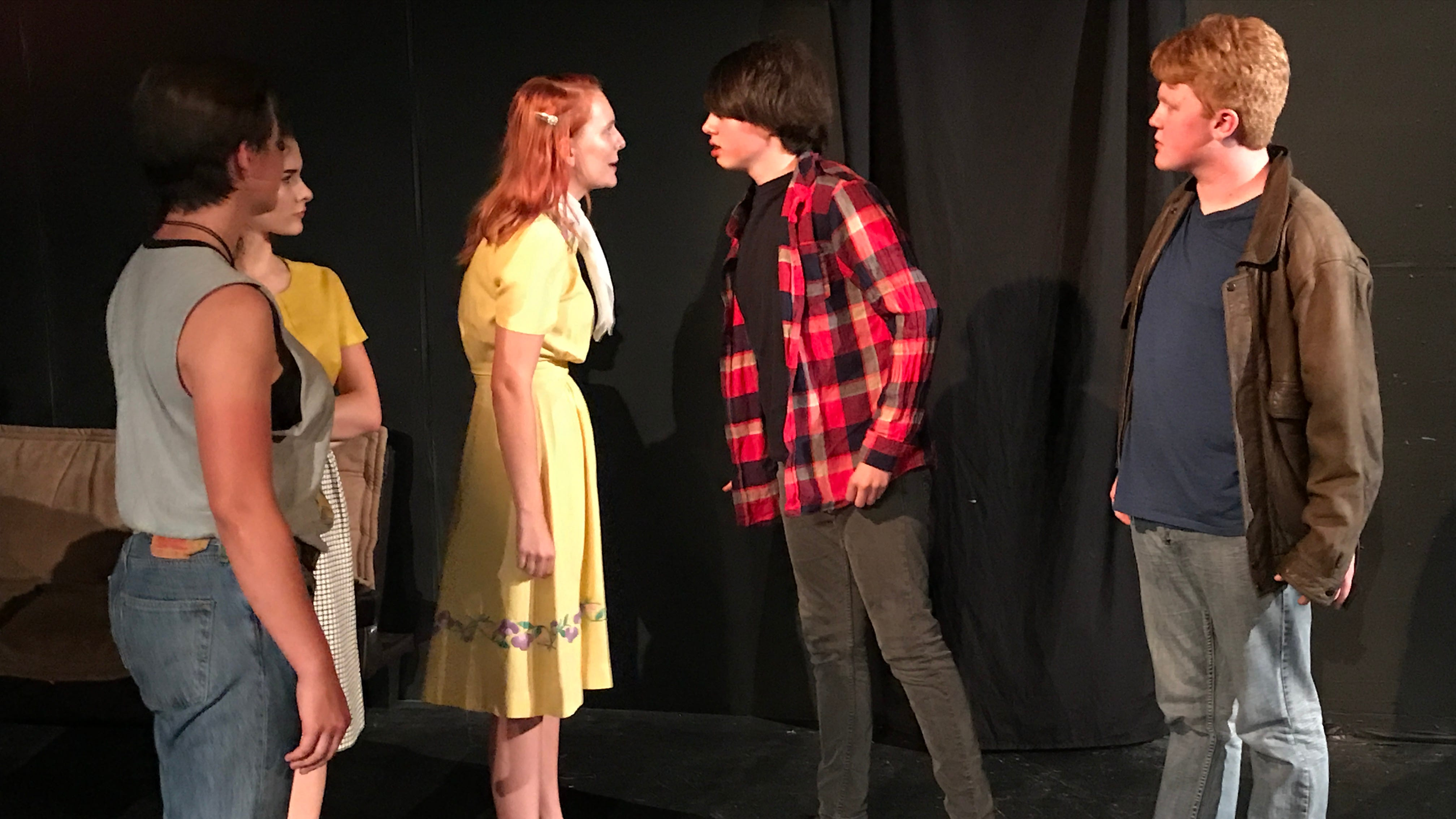 """Tempers flare as Cherry (Kathlyn Smith, yellow dress) confronts Bob (Robert Burke, checkered shirt) in a scene from """"The Outsiders."""""""