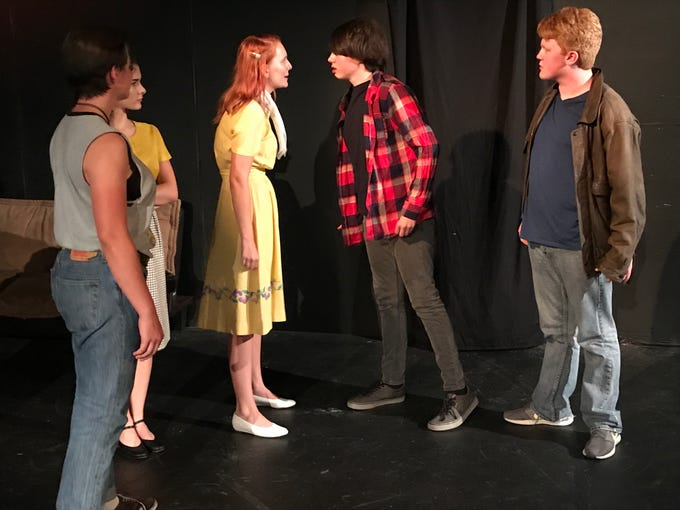 "Tempers flare as Cherry (Kathlyn Smith, yellow dress) confronts Bob (Robert Burke, checkered shirt) in a scene from ""The Outsiders."""