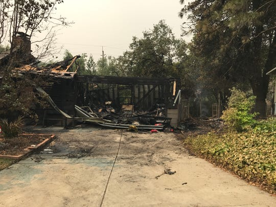 A charred home on Redbud Drive smolders July 27, 2018 after the Carr Fire swept through the area.