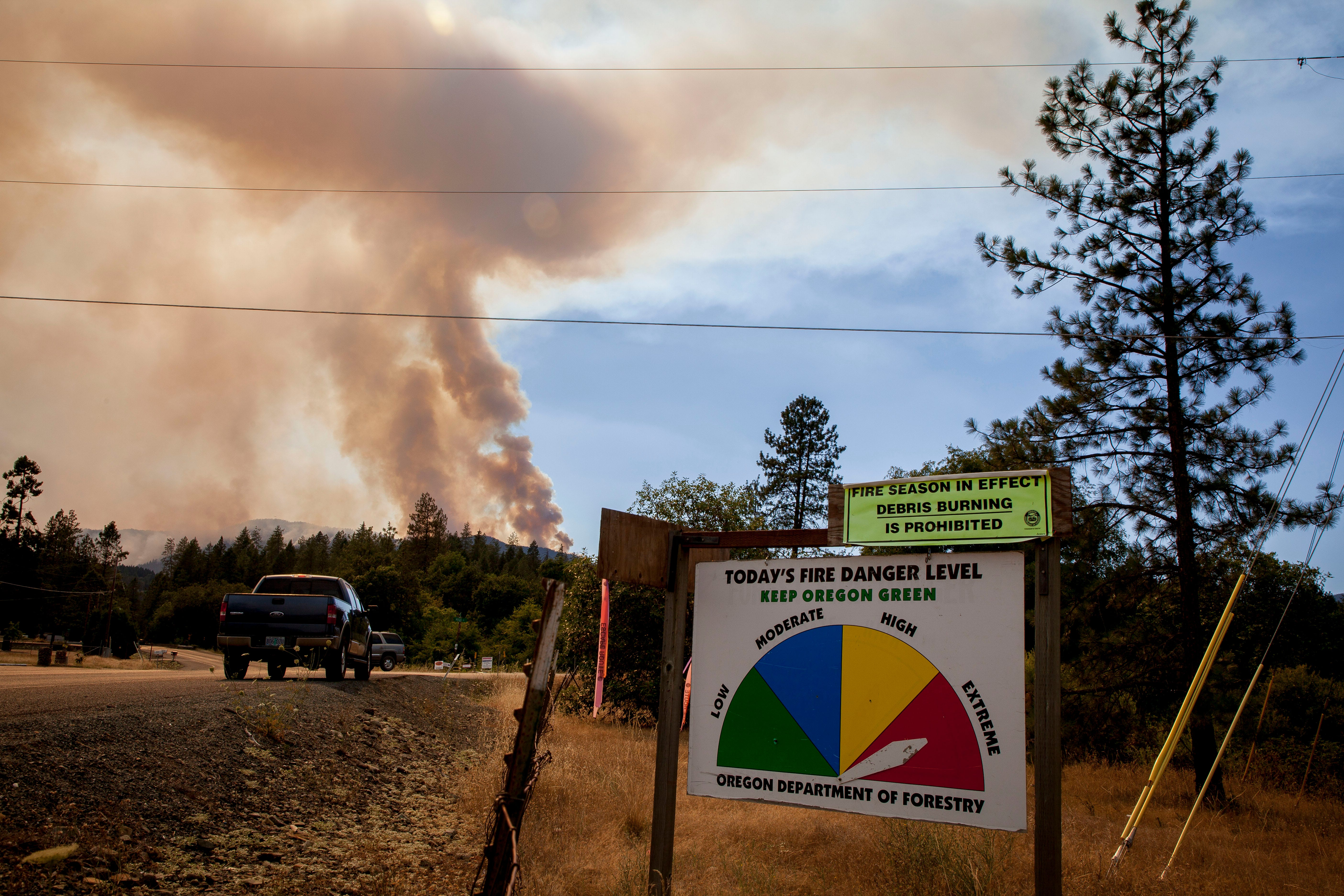 A fire level danger sign shows extreme fire danger along Galice Road just west of Merlin in southern Oregon as smoke rises from Taylor Creek wildfire in the Siskiyou National Forest near the Rogue River in July, 2018.  Smoke caused air quality to be compromised.