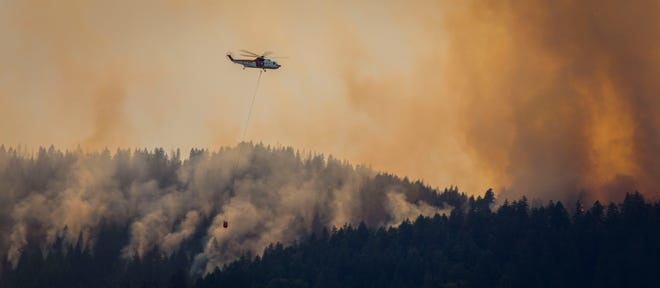 A helicopter flies through smoke as it rises from a wildfire in the Siskiyou National Forest near the Rogue River on Thursday,  July 26.
