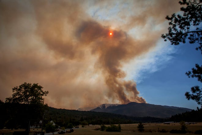 Smoke is seen from Galice Road just west of Merlin in southern Oregon as it rises from Taylor Creek wildfire in the Siskiyou National Forest near the Rogue River Thursday afternoon, July 26, 2018. Several helicopters were working the fire. Smoke has caused air quality to be compromised due to several fires burning in the southern Oregon area.