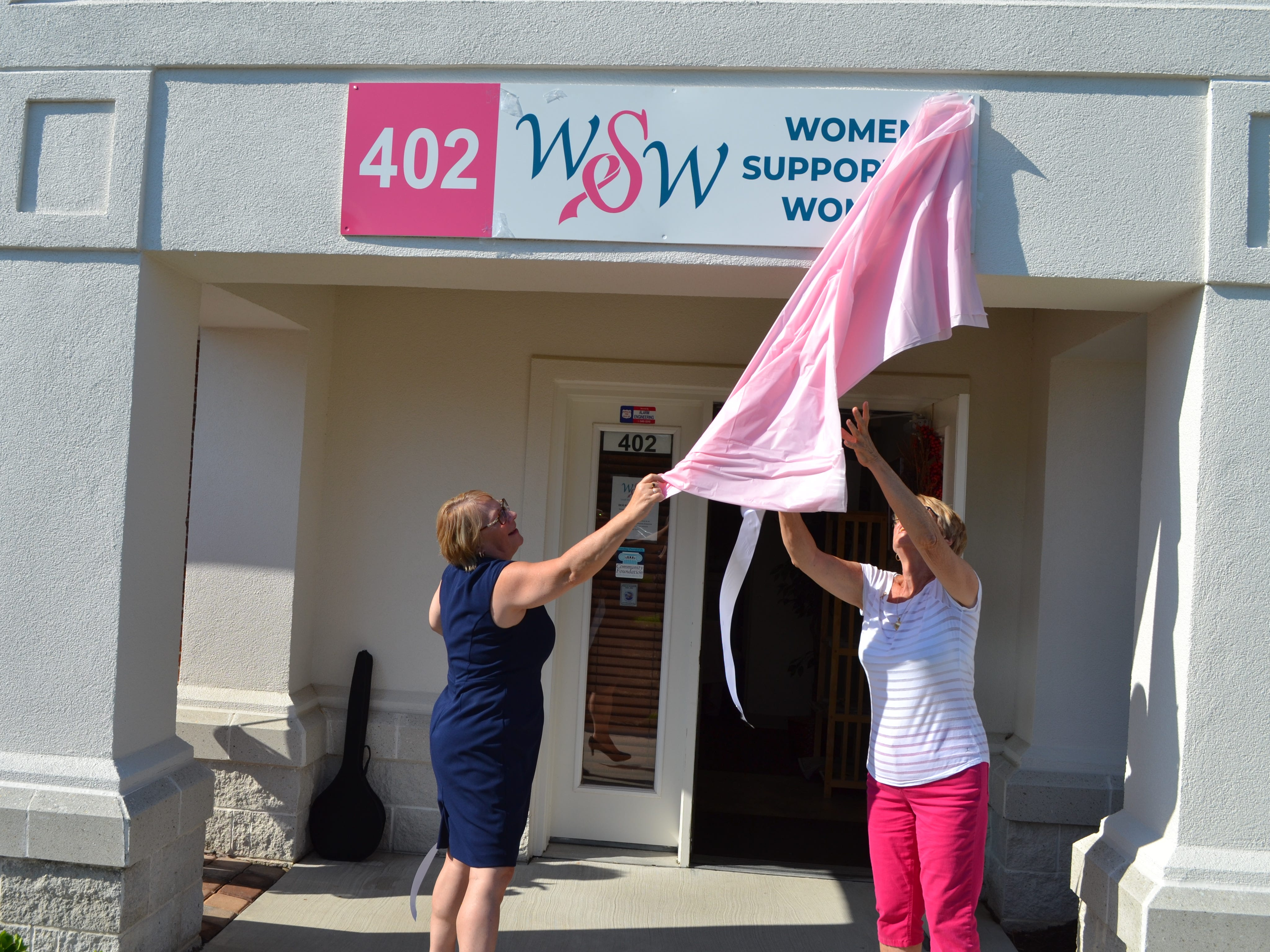 Cindy Feist, left, executive director of Women Supporting Women, and founder Sue Revelle unveil a sign with the breast cancer support organization's 25th anniversary party on Thursday, July 26.