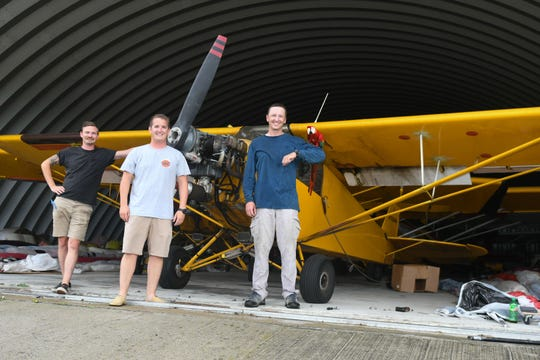 Pilots Paul Hofmann, Rob Cushen, and Justin hildenbrandt holding tamale stand in front of one of the banner planes owned by Ocean Aerial Ads in Berlin, Md. on Tuesday, July 24, 2018.