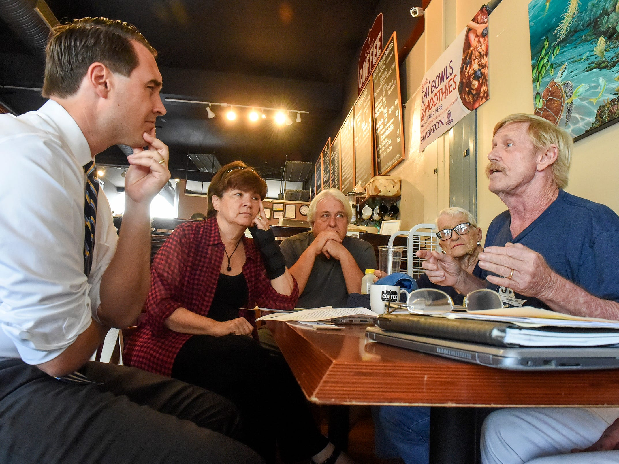 "Florida gubernatorial candidate Chris King listens as Martin County residents voice their concerns over toxic discharges into local waterways Friday, July 27, 2018, during an ""algae roundtable"" discussion at the Stuart Coffee Company in downtown Stuart."