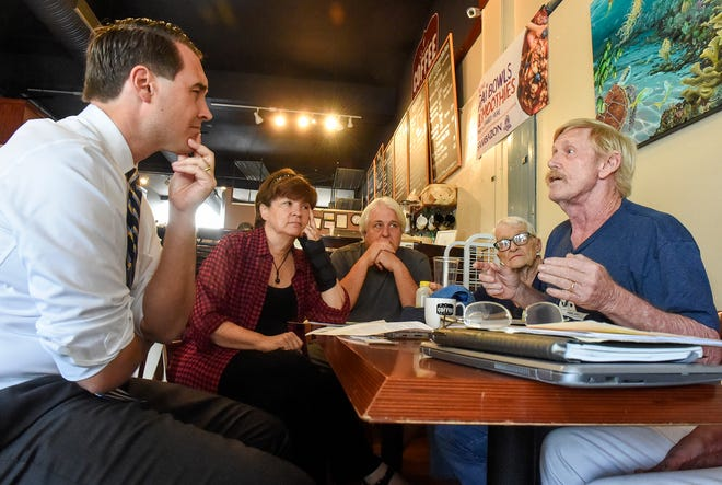 """Florida gubernatorial candidate Chris King listens as Martin County residents voice their concerns over toxic discharges into local waterways Friday, July 27, 2018, during an """"algae roundtable"""" discussion at the Stuart Coffee Company in downtown Stuart."""
