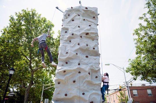 Students from Cumberland County Tech climb a rock wall during a Play Streets event with Vineland police, fire and EMS Friday, July 27, 2018 in Vineland, N.J.