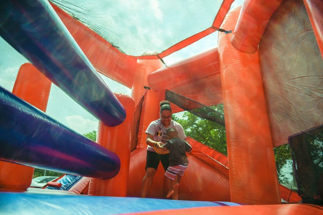 Janika Echevarria, 20, plays in a bounce house with her little brother Kevarry Collins, 2, during a Play Streets event with Vineland police, fire and EMS departments Friday, July 27, 2018 in Vineland, N.J.