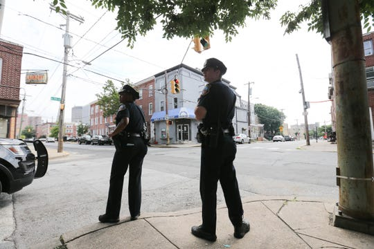 Officers Danielle Moore, left, and Will Martin patrol the West Center City neighborhood of Wilmington Friday, July 27.