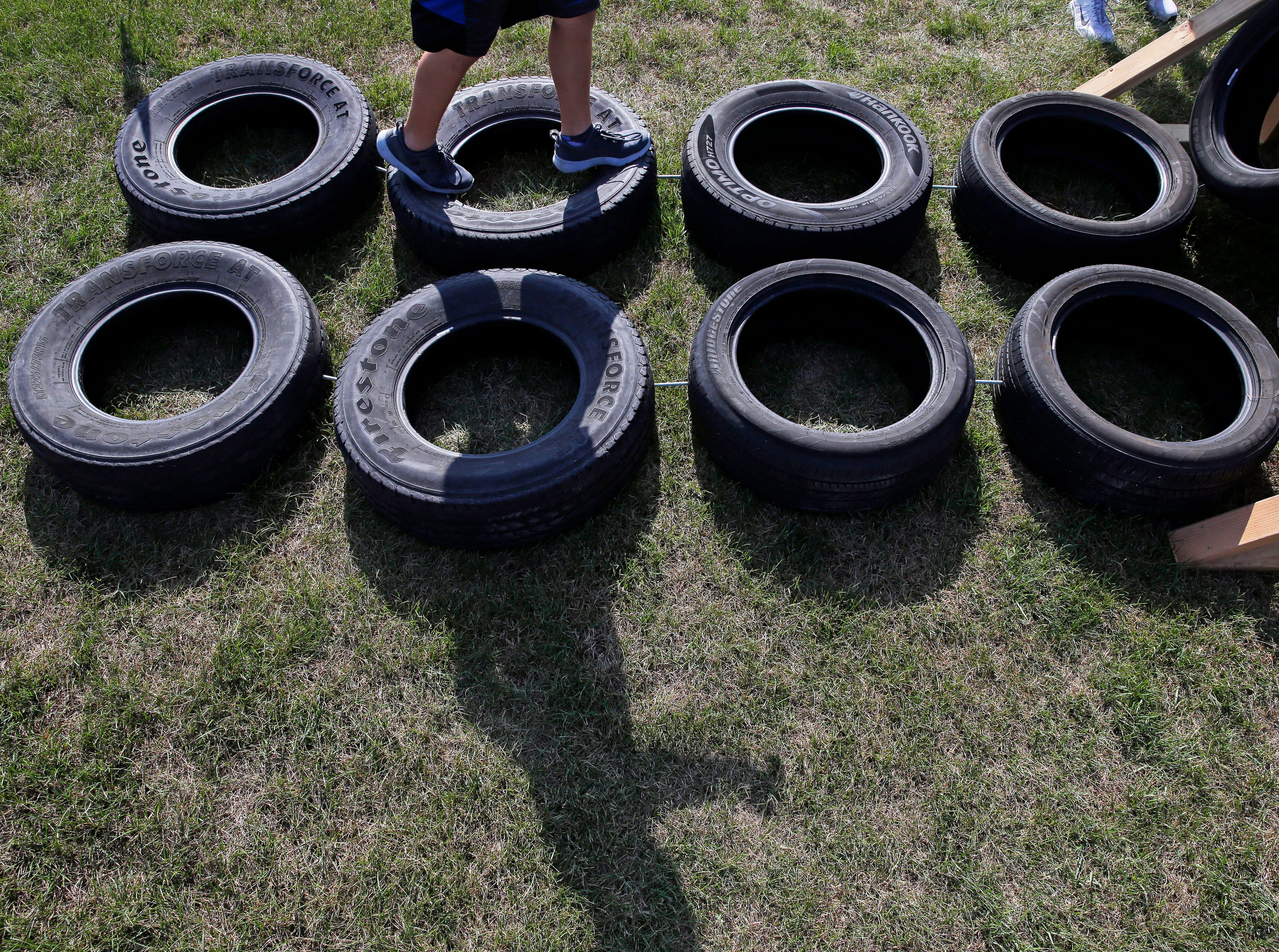 A runner goes over the tires as Cole's Cancer Crusade, an obstacle course for kids takes place Saturday, July 28, 2018, at Appleton East High School in Appleton, Wis. The event raised funds for the Snowdrop Foundation Wisconsin Chapter.