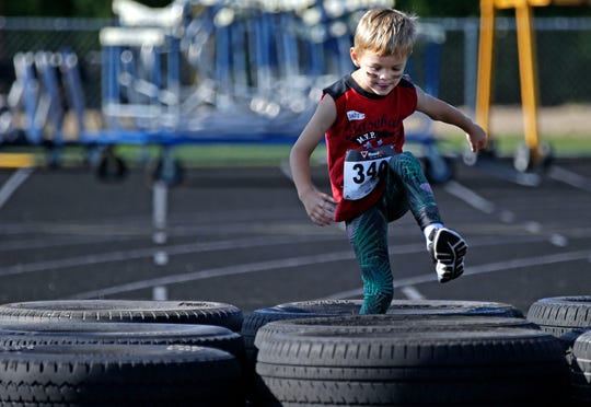 Quinn Dunham of Neenah steps through a tire obstacle as Cole's Cancer Crusade, an obstacle course for kids takes place Saturday, July 28, 2018, at Appleton East High School in Appleton, Wis. The event raised funds for the Snowdrop Foundation Wisconsin Chapter.