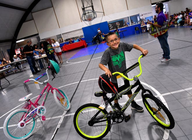 Gideon Garza, 7, wheels way his new bicycle during Saturday's LULAC Back to School Rally at Sears Park. Gideon said he was especially happy to win the bicycle, his previous one had been stolen last year.
