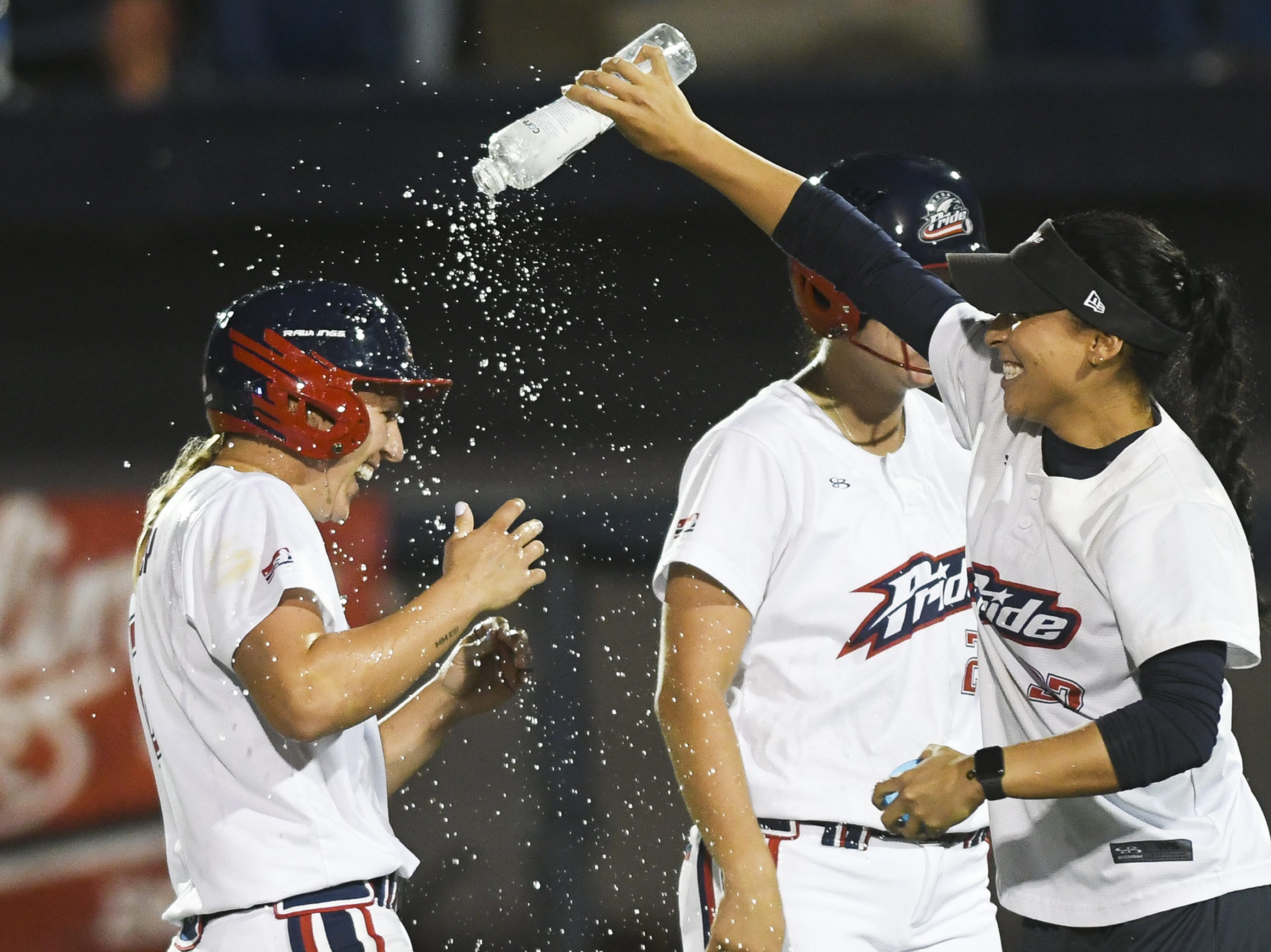 Shelby Pendley of the USSSA Pride gets a shower after drawing a bases loaded walk to score teammate and win the game against Chicago Friday in Viera.