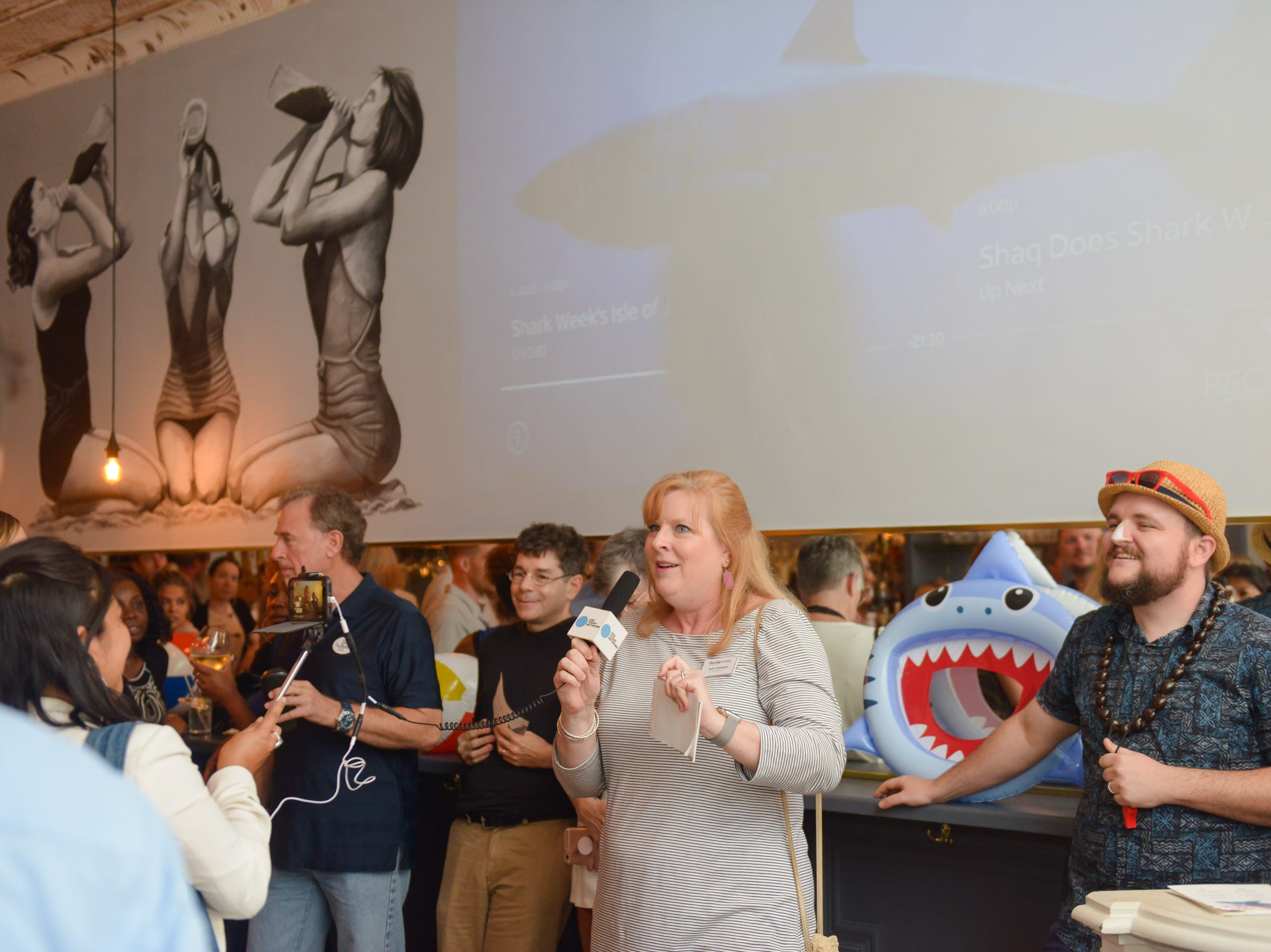 Suzy Leonard toasts to sharks at a community gathering to kick off Shark Week, hosted by Florida Today at Crush XI in downtown Melbourne.