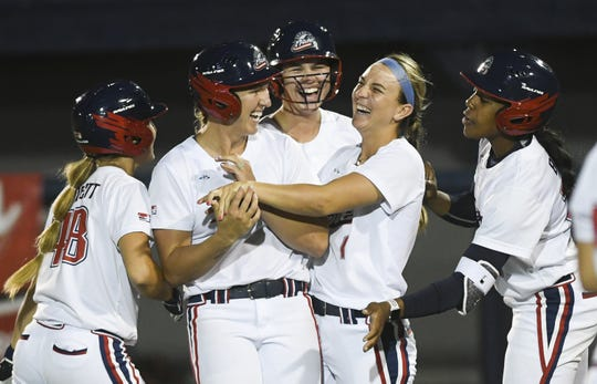 Shelby Pendley  and Nicole DeWitt of the USSSA Pride are mobbed by teammates after a bases loaded walk to win the game against Chicago Friday in Viera.