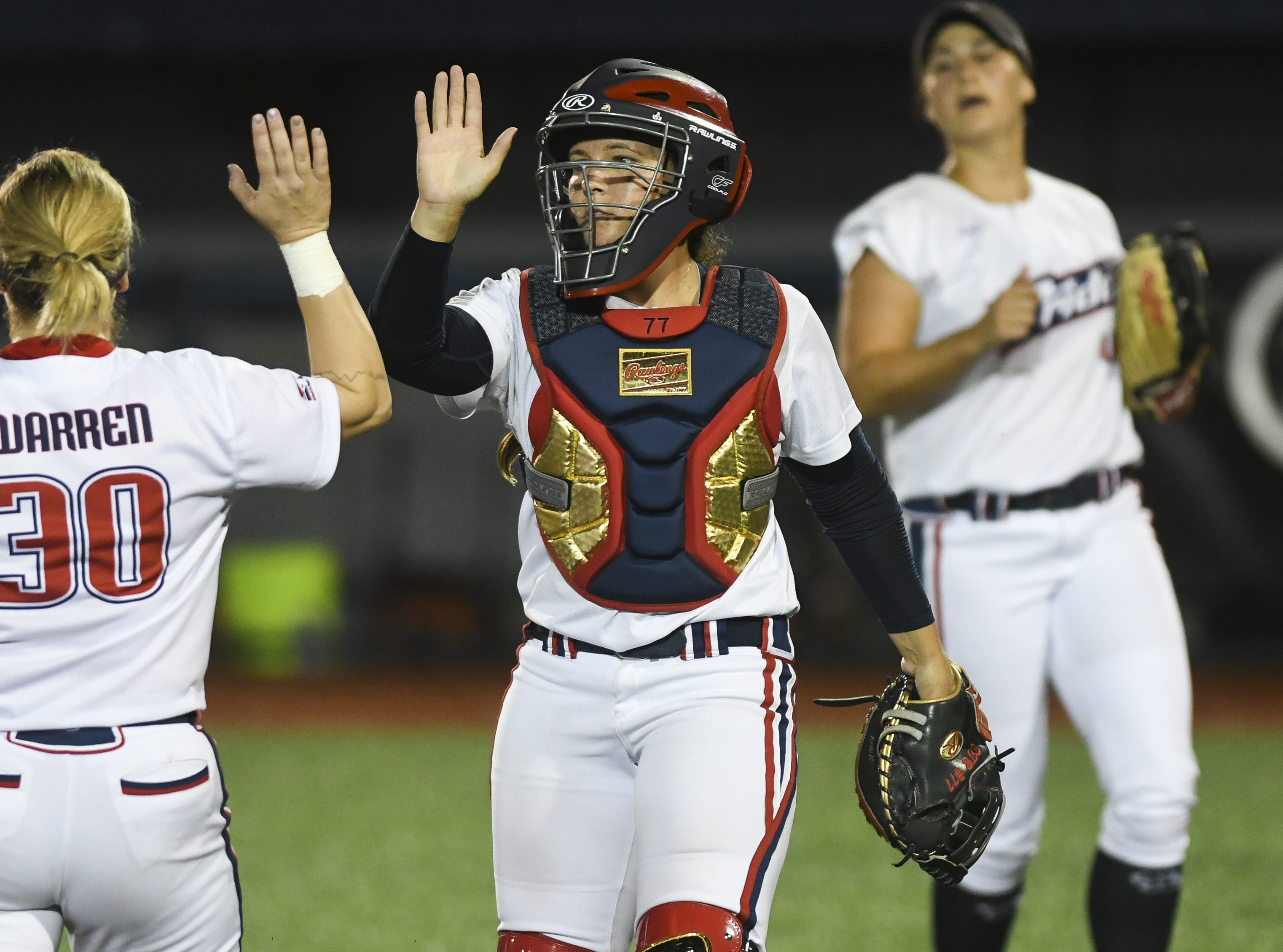 Jessie Warren of the Pride high fives catcher Chelsea Goodacre during Friday's game in Viera.