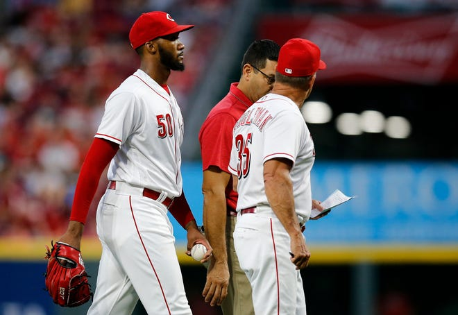 Cincinnati Reds relief pitcher Amir Garrett (50) leaves the game with a lower leg injury in the firth inning of the MLB National League game between the Cincinnati Reds and the Philadelphia Phillies at Great American Ball Park in downtown Cincinnati on Friday, July 27, 2018. The Reds won 6-4.