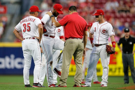 Cincinnati Reds relief pitcher Amir Garrett (50) is checked by trainer Tomas Vera in the fifth inning of the MLB National League game between the Cincinnati Reds and the Philadelphia Phillies at Great American Ball Park in downtown Cincinnati on Friday, July 27, 2018. The Reds won 6-4.