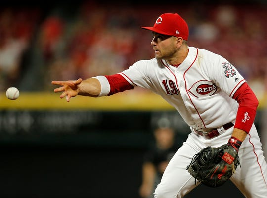 Cincinnati Reds first baseman Joey Votto (19) tosses a ground ball to relief pitcher Jared Hughes (48) for a force out in the eighth inning of the MLB National League game between the Cincinnati Reds and the Philadelphia Phillies at Great American Ball Park in downtown Cincinnati on Friday, July 27, 2018. The Reds won 6-4.