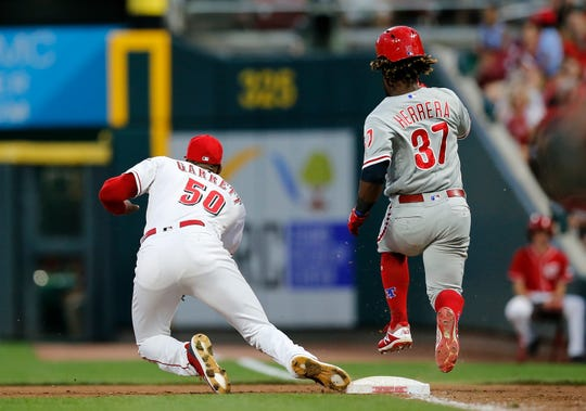 Cincinnati Reds relief pitcher Amir Garrett (50) tumbles after tagging the force out of Philadelphia Phillies center fielder Odubel Herrera (37) in the fifth inning of the MLB National League game between the Cincinnati Reds and the Philadelphia Phillies at Great American Ball Park in downtown Cincinnati on Friday, July 27, 2018. The Reds won 6-4.