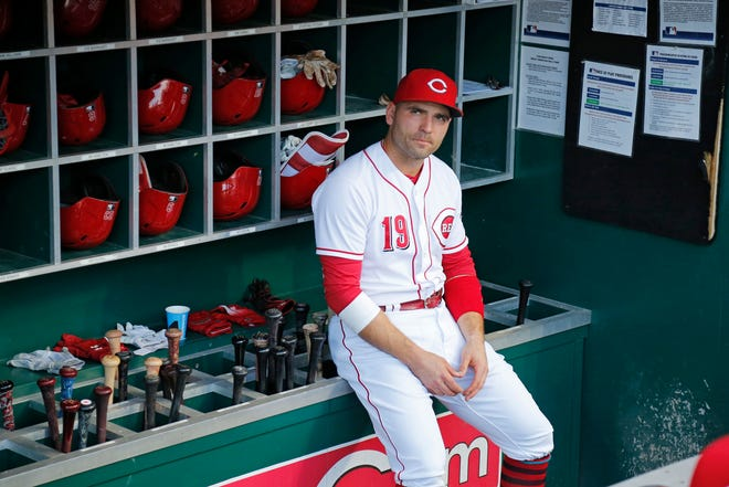 Cincinnati Reds first baseman Joey Votto (19) sits in the dugout before being introduced ahead of the first inning of the MLB National League game between the Cincinnati Reds and the Philadelphia Phillies at Great American Ball Park in downtown Cincinnati on Friday, July 27, 2018.