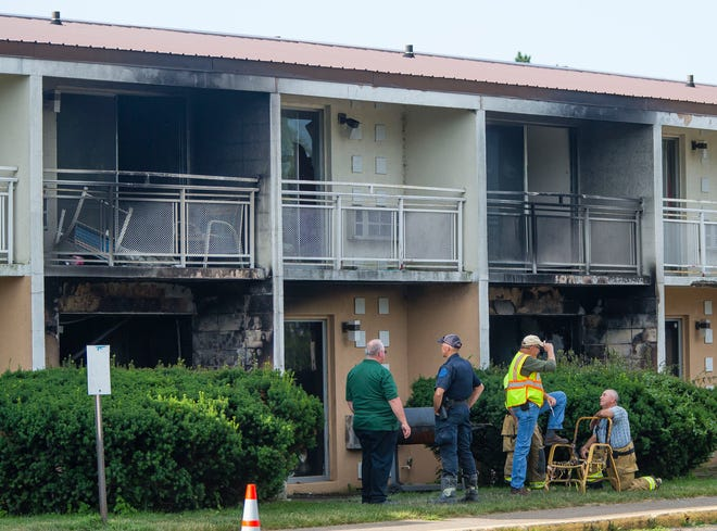Officials investigate at a fire at the Cosmo Extended Stay Motel in Sodus Township, Mich., on Saturday, July 28, 2018.  A fire swept through the southwestern Michigan motel early Saturday, killing several members of the same family, including a woman and her children, authorities said.
