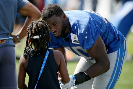 Linebacker Jarrad Davis signs an autograph after the Detroit Lions training camp at their practice facility in Allen Park on Sat. July 28, 2018.