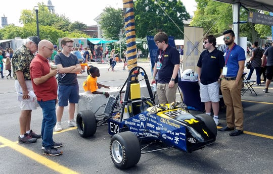 Brian Vera-Burgos, third from right, shows off the University of Michigan Dearborn's electric car during the Maker Faire at The Henry Ford Museum in Dearborn on Saturday, July 28,  2018.