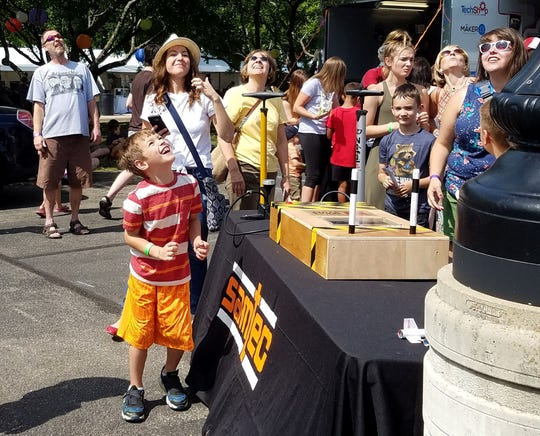 Caleb, 7, and his mother Laura, 35, from Rochester Hills peer at the sky after launching a paper rocket during the Maker Faire at The Henry Ford Museum in Dearborn on Saturday, July 28,  2018.