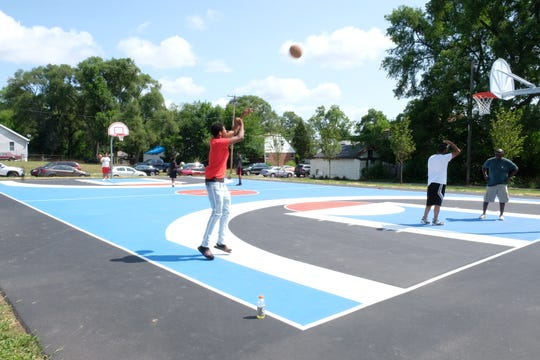 Teens play on the new basketball court during opening of Ella Fitzgerald Park Saturday, July 28.