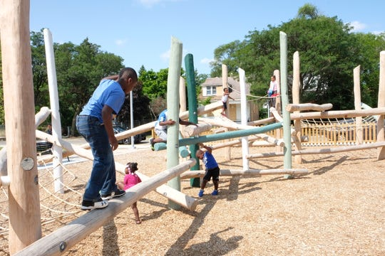 Children play on balance jungle gym during opening of Ella Fitzgerald Park Saturday, July 28.