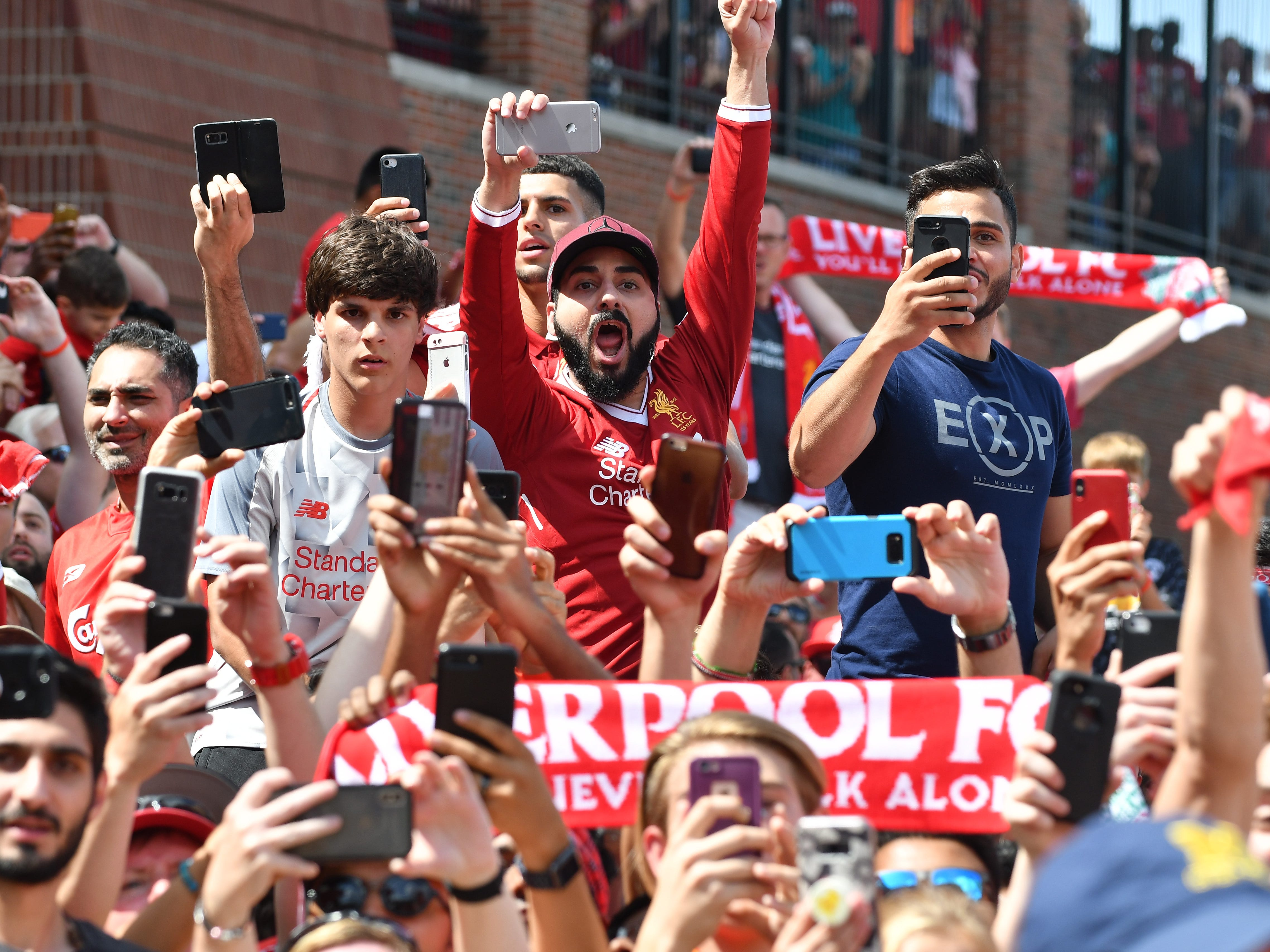 Crowds react as Manchester United and Liverpool buses arrive for the International Champions Cup game  at Michigan Stadium on the campus of University of Michigan in Ann Arbor, Michigan on July 28, 2018.