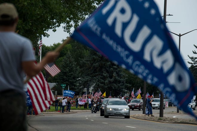 """Loveland resident Kye Brittell waves a Trump flag at the """"I Stand With Trump! - MAGA Rally"""" on Eisenhower Boulevard on Saturday, July 28, 2018, in Loveland, Colo."""