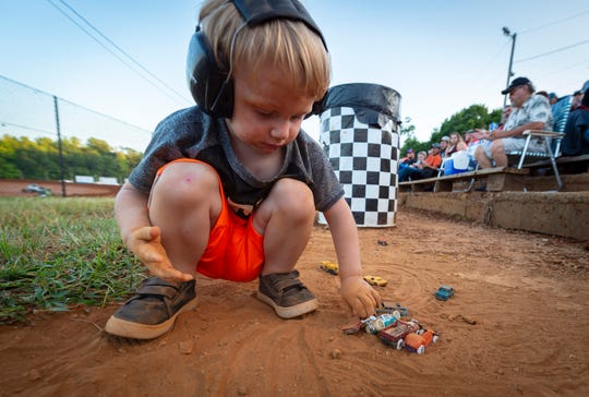 Wearing his sound dampening headphones, Kayden White, 2, of Springfield, Ind., recreates his own version of dirt-track racing with his toy cars in some dirt near the stands. Many parents keep ear protection on their children as the loud race cars are on the track. Drivers competed in the sixth of seven races of the 31st Annual Indiana Sprint Week, part of the 2018 USAC AMSOIL National Sprint Car season, at Bloomington Speedway, Friday, July 27, 2018.