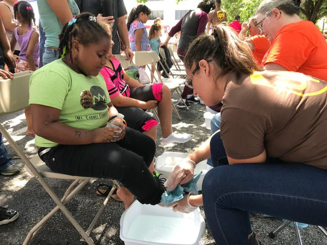 Volunteer Elizabeth Rambo washes and dries 6-year-old Kyreh Edwards' feet before she tries on shoes at the Indianapolis Urban League's Back-to-School Block Party on Saturday, July 28, 2018.