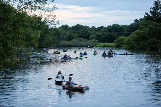 Paddlers make their way down the Manitowoc River to Lake Michigan during a moonlight paddle to view the full moon on July 27, 2018, in Manitowoc, Wis.