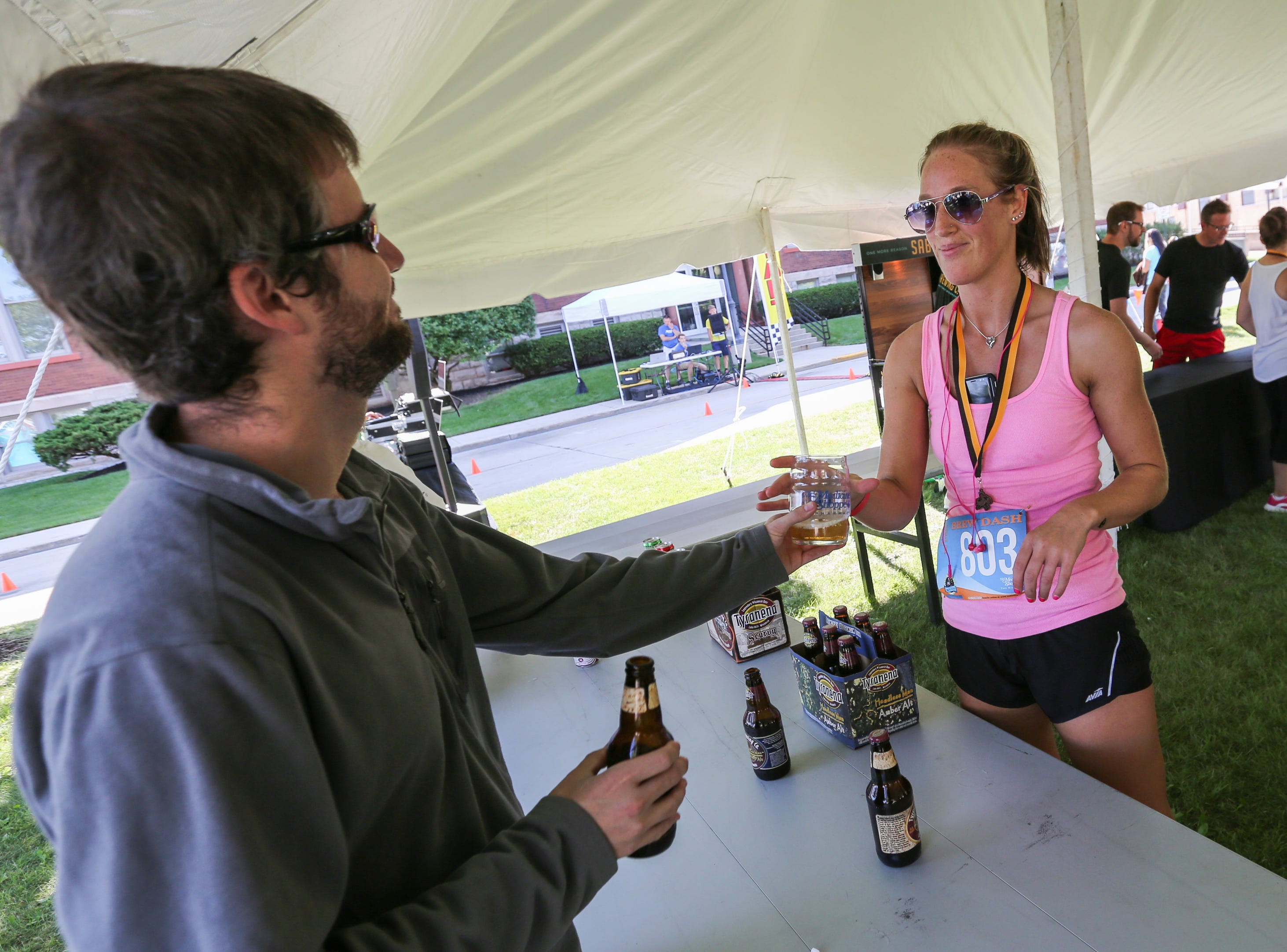 A volunteer hands Angie Boness a beer after she ran the 5K Brew Dash Saturday, July 28, 2018, in Two Rivers, Wis. Josh Clark/USA TODAY NETWORK-Wisconsin