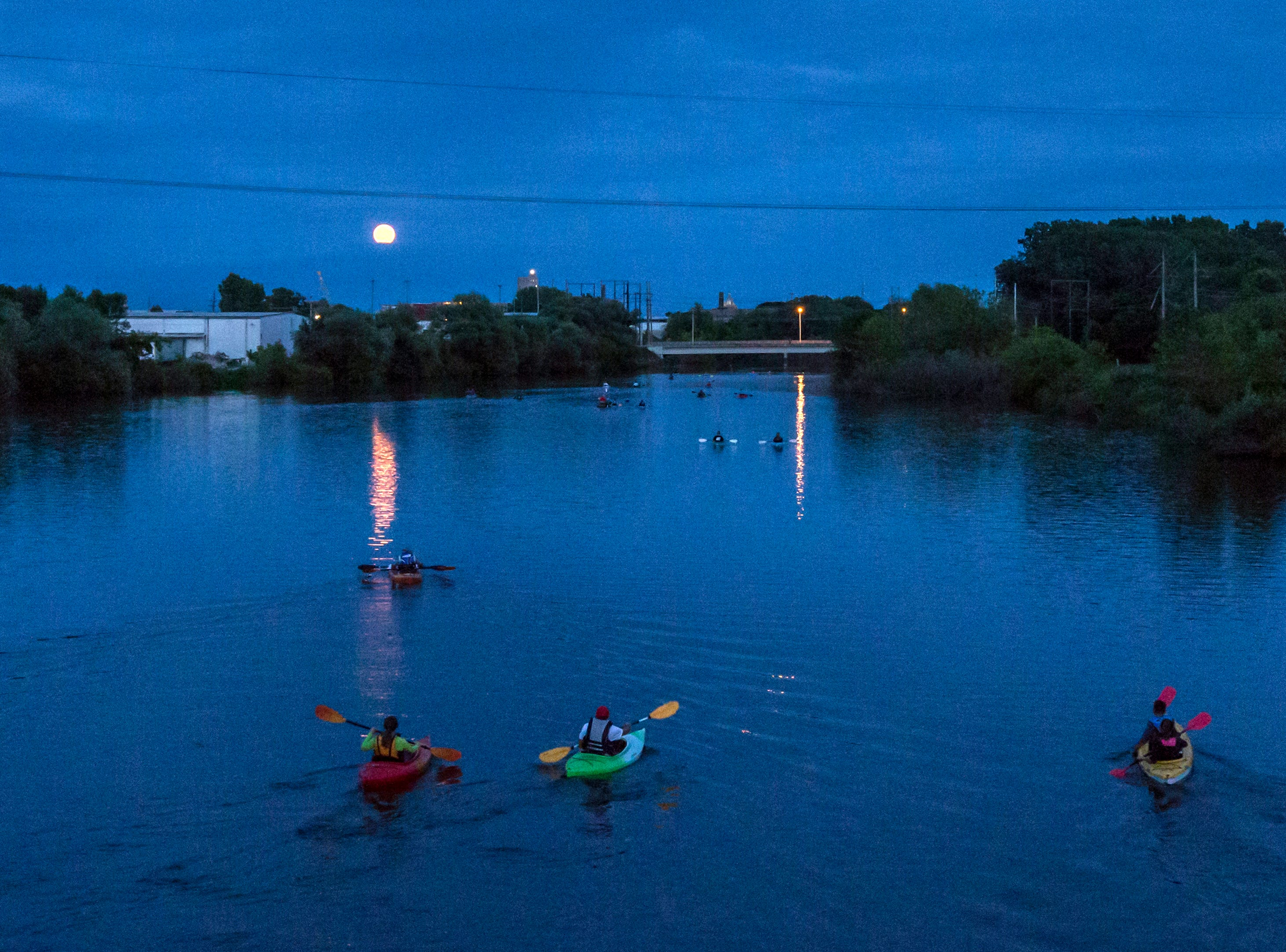 Paddlers make their way down the Manitowoc River as a full moon rises over the horizon Friday, July 27, 2018, in Manitowoc, Wis. Josh Clark/USA TODAY NETWORK-Wisconsin