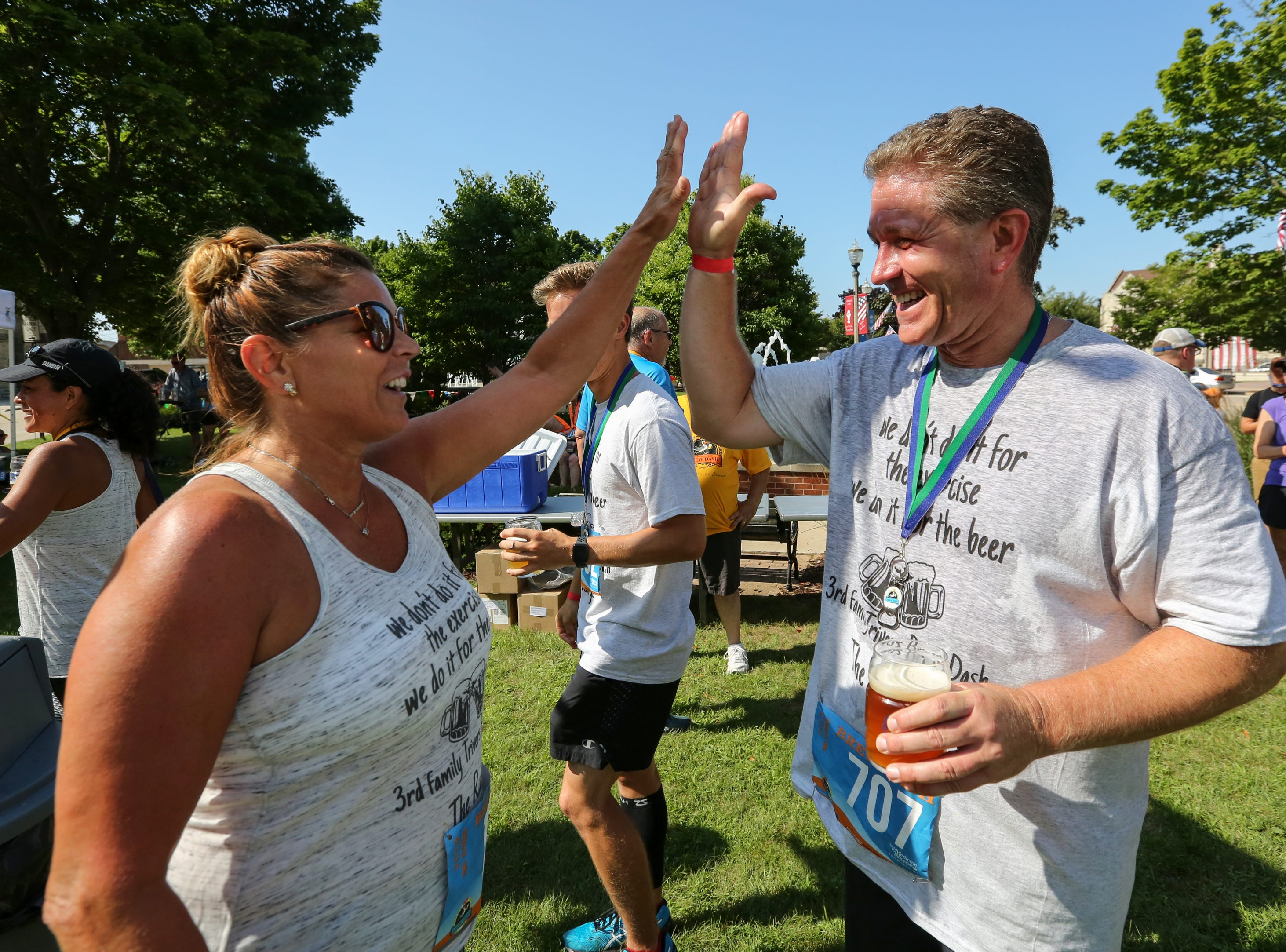 Tammy Marnocha high fives Jon Rudebeck after running the Brew Dash 5K Saturday, July 28, 2018, in Two Rivers, Wis. Josh Clark/USA TODAY NETWORK-Wisconsin