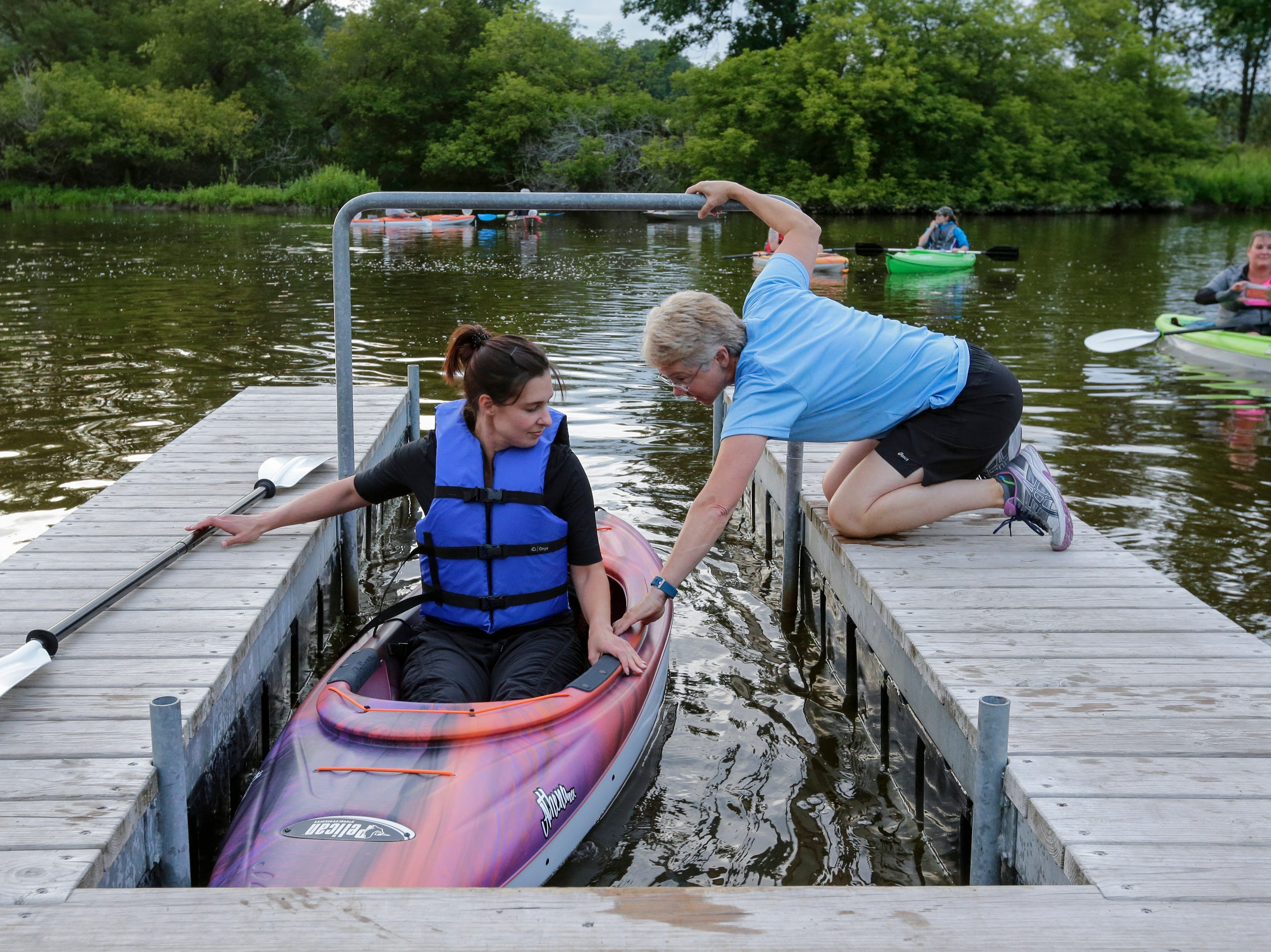 Kim Kettner, right, helps Steph Evenson into her kayak as paddlers set out at Lower Henry Schuette Park for a full moon paddle down the Manitowoc River Friday, July 27, 2018, in Manitowoc, Wis. Josh Clark/USA TODAY NETWORK-Wisconsin