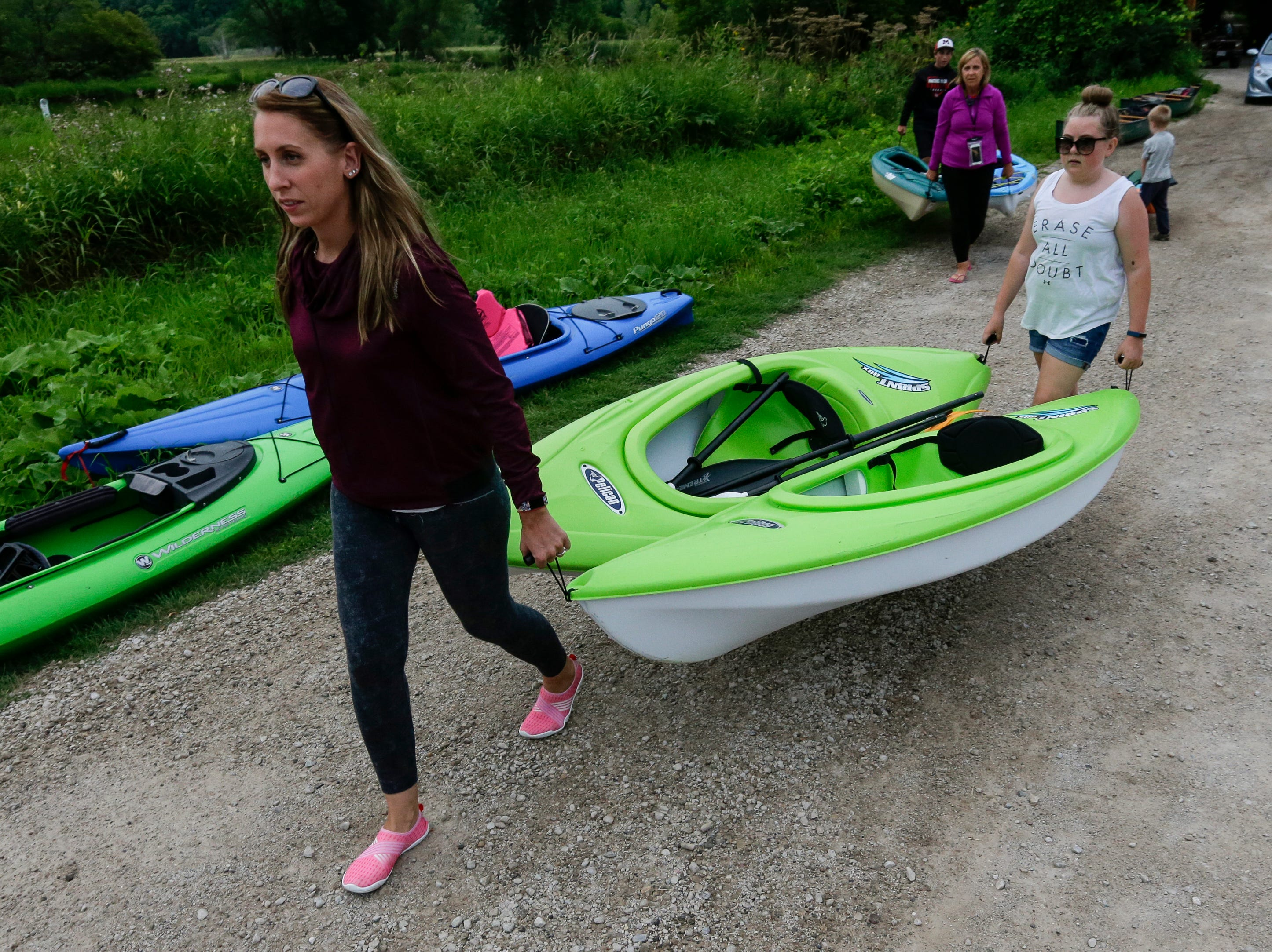 Nicole Zortman and her daughter Hailey, 12, carry their kayaks down to the launch at Lower Henry Schuette Park before a moonlight paddle on the Manitowoc River Friday, July 27, 2018, in Manitowoc, Wis. Josh Clark/USA TODAY NETWORK-Wisconsin