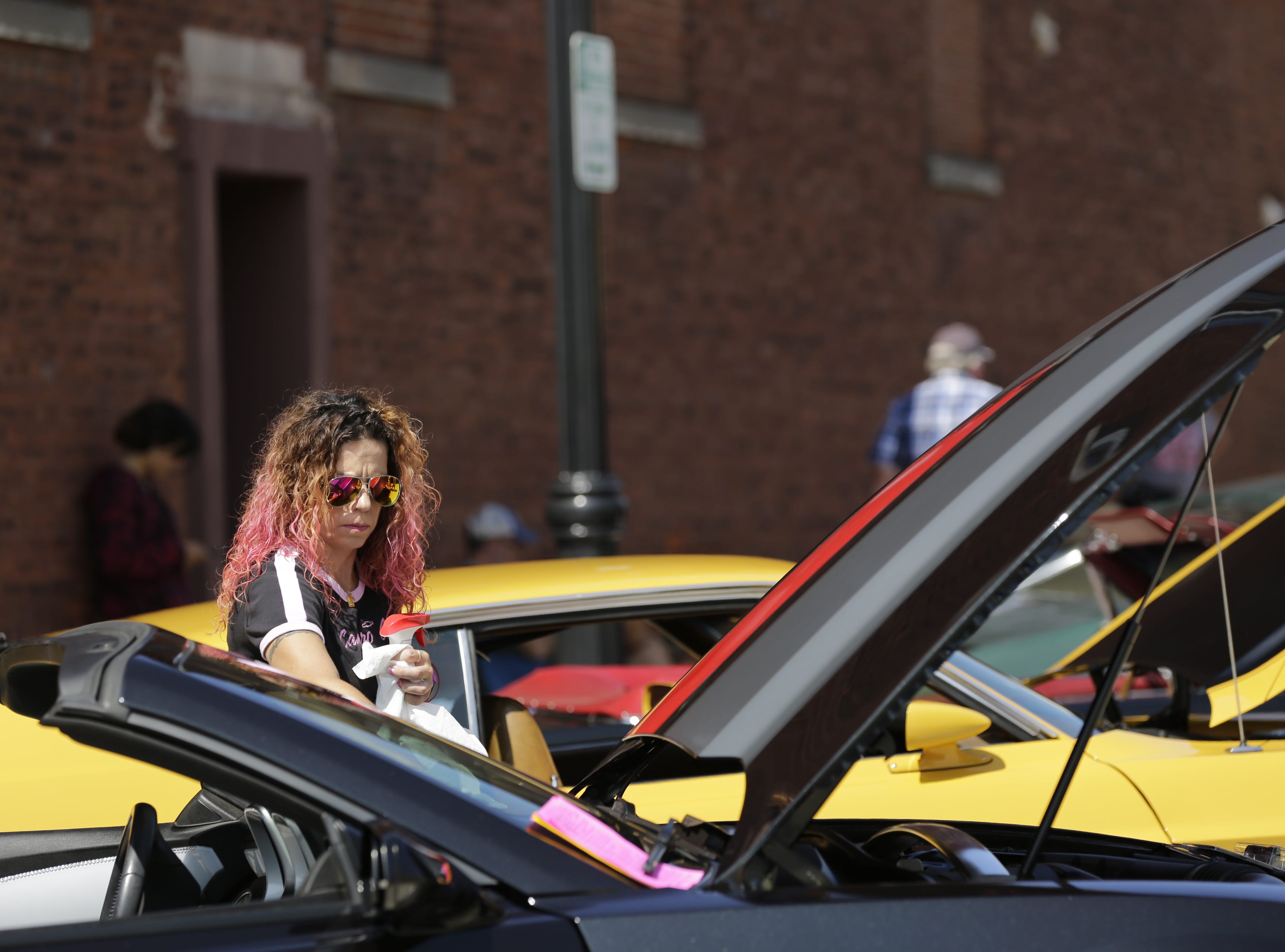 Jolene Orlowski cleans the windshield of her Camaro during the car show at Hub City Days in downtown Marshfield Saturday, July 28, 2018.