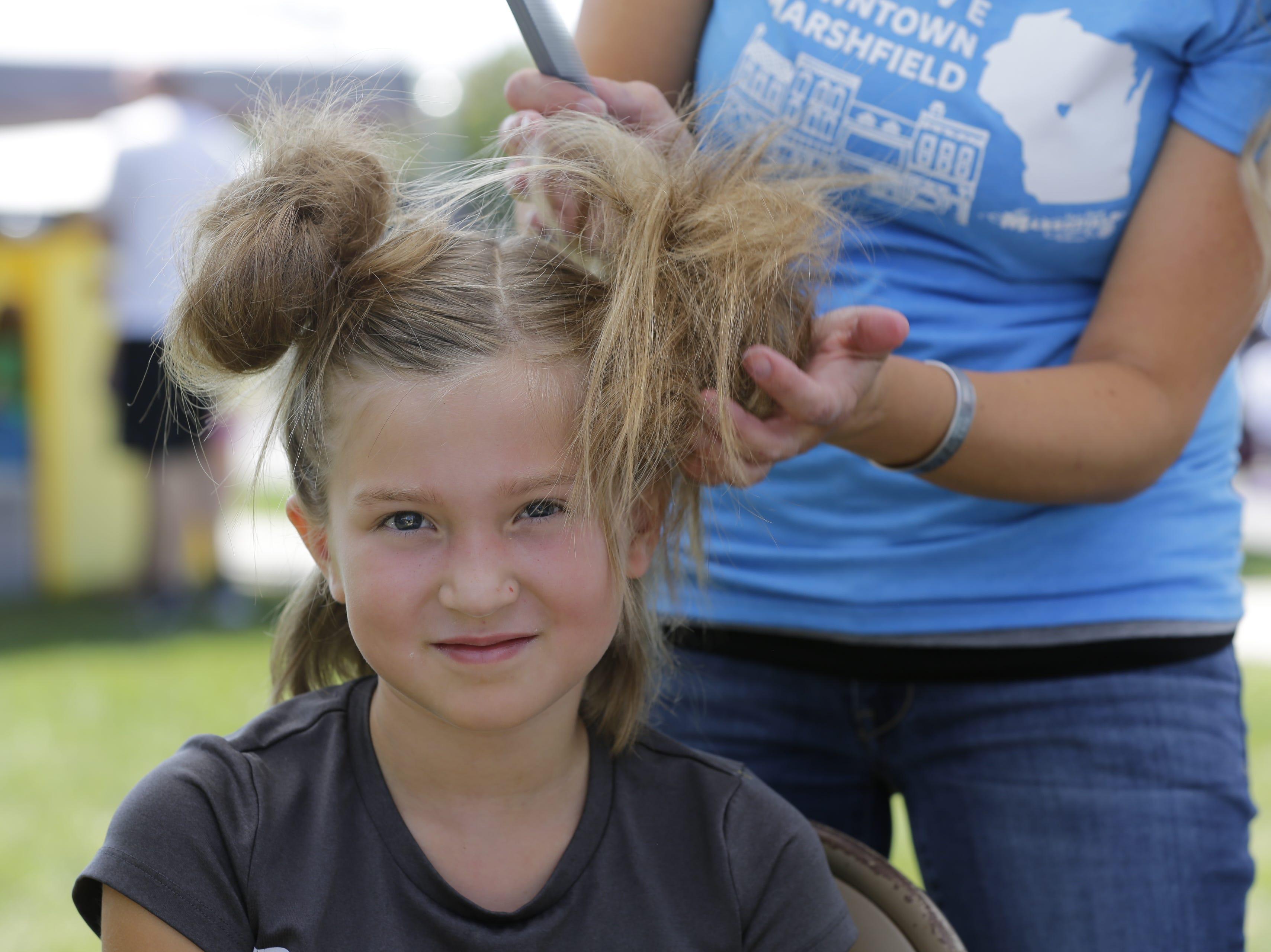 Elly Gardner, 7, of Marshfield gets crazy hair at Hub City Days in downtown Marshfield Saturday, July 28, 2018.